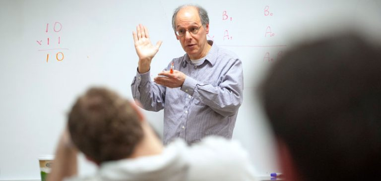Students interacting with a physics professor at the Waterbury campus
