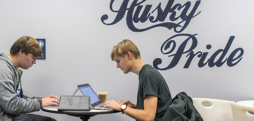 Student play a video game and work on homework in the student Lounge at UConn Waterbury